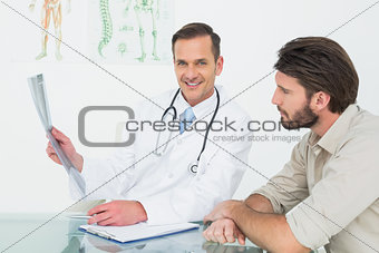 Smiling doctor explaining spine x-ray to patient