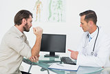 Male doctor in conversation with patient at desk