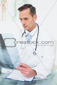 Concentrated male doctor looking at x-ray picture
