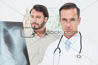 Portrait of a male doctor and patient with lungs x-ray