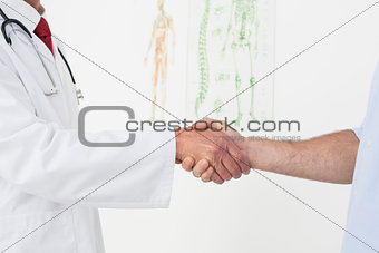 Close-up mid section of a doctor and patient shaking hands
