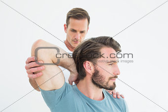 Physiotherapist stretching a young man's arm