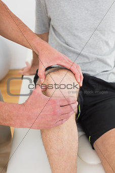 Mid section of a man getting his knee examined