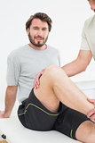 Portrait of a young man getting his knee examined