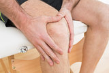 Mid section of a man with his hands on a painful knee