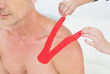 Hands putting on red kinesio tape on patient's shoulder