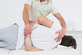Male physiotherapist examining man's back