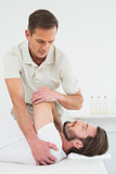 Male physiotherapist stretching a man's hand
