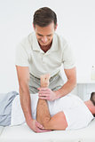 Male physiotherapist examining a man's hand