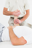 Mid section of physiotherapist examining a man's hand