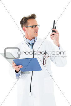 Annoyed doctor with clipboard talking on wireless radio