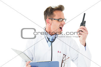 Annoyed doctor with clipboard shouting into a wireless radio