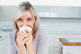 Casual young woman drinking coffee at home