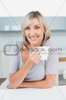 Smiling casual young woman with coffee cup in kitchen