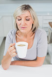 Casual young woman drinking coffee in kitchen