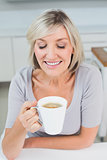 Close-up of a woman drinking coffee in kitchen