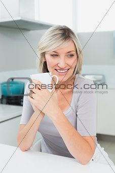 Thoughtful smiling woman with coffee cup in kitchen