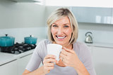 Smiling casual woman with coffee cup in kitchen