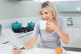 Woman drinking coffee while reading newspaper in kitchen