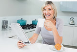 Happy woman with coffee cup and newspaper in kitchen