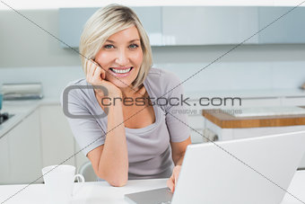 Casual woman with coffee and laptop in kitchen