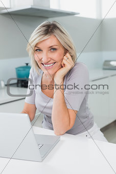 Casual happy woman with laptop in kitchen