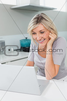 Casual happy woman using laptop in kitchen