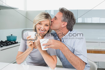 Loving couple with coffee cups in kitchen