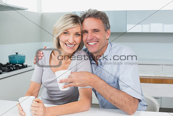 Happy loving couple with coffee cups in kitchen