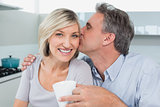 Man kissing a happy woman's cheek in kitchen