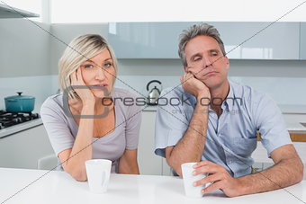 Bored couple sitting with coffee cups in kitchen