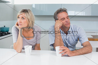 Displeased couple sitting with coffee cups in kitchen