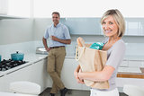 Smiling woman with grocery bag and man in background at kitchen