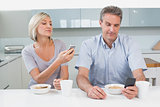 Couple reading text messages while having breakfast