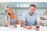 Couple with cellphones while having breakfast