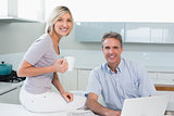 Couple with coffee cup and laptop in kitchen