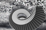 Winding staircase in the sky with flying papers