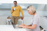 Woman using laptop and man with coffee cup at kitchen