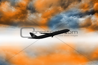 Airplane flying over orange sky