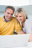 Happy casual couple using laptop in kitchen
