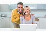 Happy casual couple with laptop in kitchen