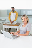 Woman using laptop and man chopping vegetables