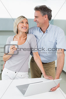 Happy loving couple with laptop in kitchen