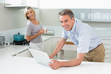 Happy man and woman with laptop in the kitchen