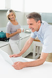Man using laptop with woman in the kitchen