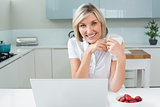 Casual woman with coffee cup and laptop in kitchen