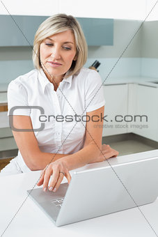 Casual woman using laptop in kitchen