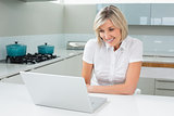 Casual woman using laptop in the kitchen