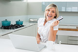 Cheerful woman doing online shopping in kitchen