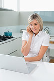 Casual woman using laptop while on call in kitchen